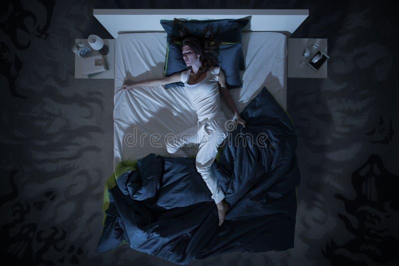 失眠和恶梦在床上在晚上 免版税库存图片