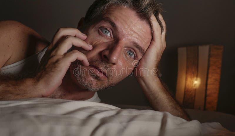 失眠和醒的可爱的人接近的面孔画象有眼睛的大开在说谎在床遭受的失眠睡觉的晚上 免版税库存图片