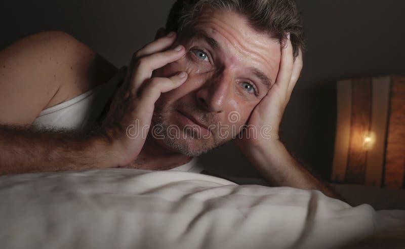 失眠和醒的可爱的人接近的面孔画象有眼睛的大开在说谎在床遭受的失眠睡觉的晚上 库存照片