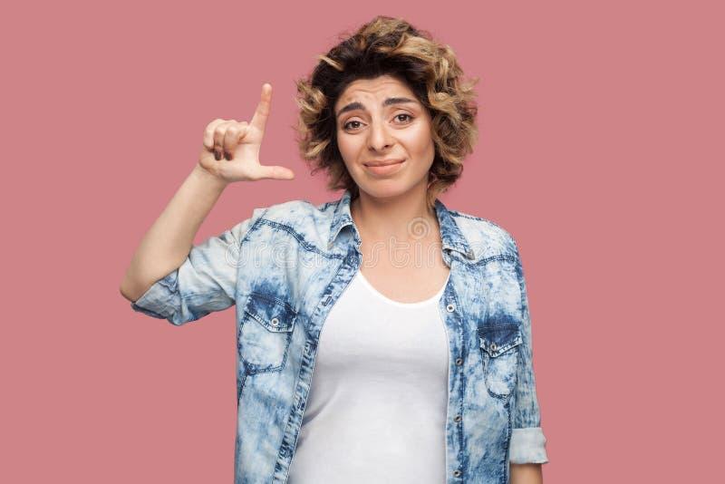 失败者 哀伤的年轻女人画象有卷曲发型的在与失败者姿态的偶然蓝色衬衣身分和看照相机 免版税库存照片