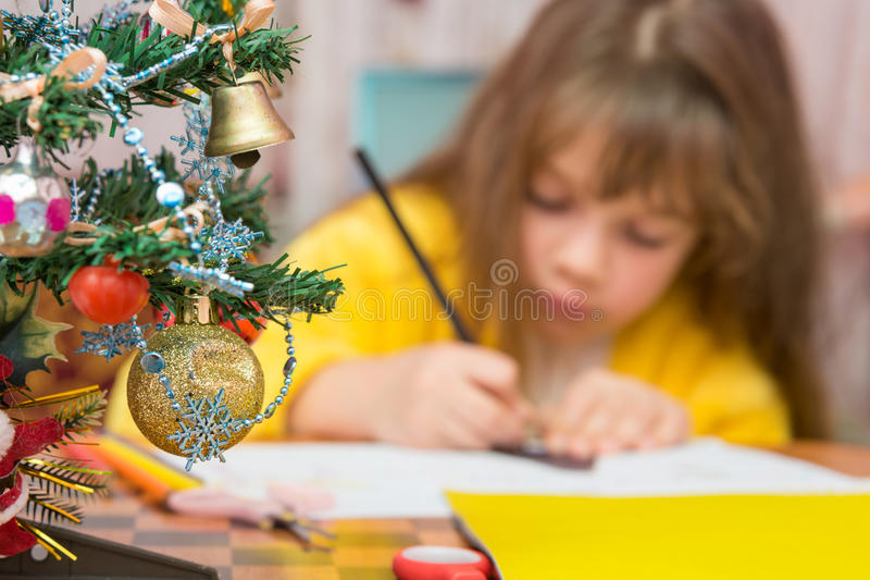 失去控制由做圣诞节工艺的女孩,集中于毛皮树 库存图片