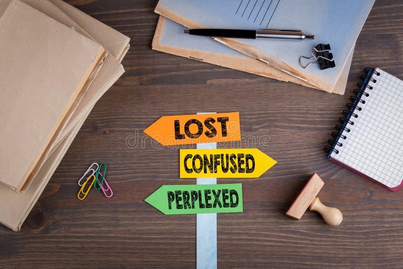 失去,迷茫和为难的概念 在一张木书桌上的纸路标 库存图片