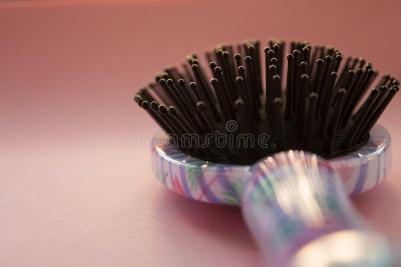 头发按摩与把柄的梳子刷子在桃红色淡色拷贝空间背景的所有类型的 Minimalistic?? 免版税图库摄影