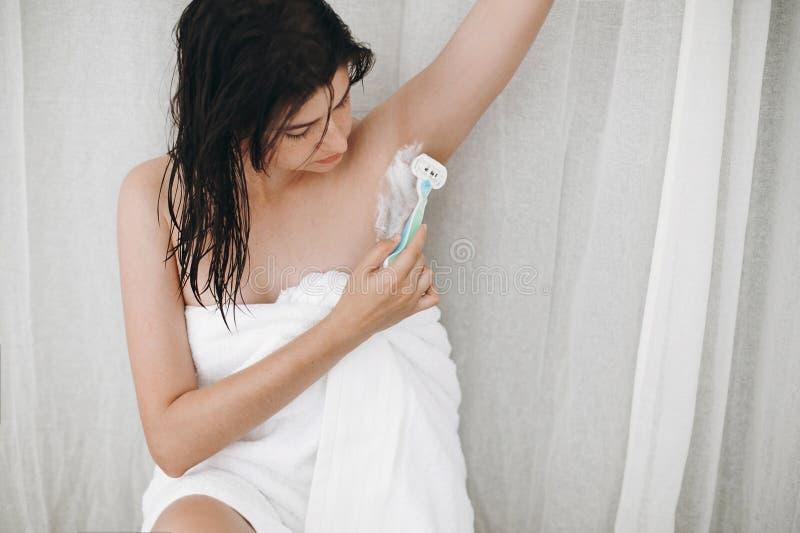 头发撤除概念 复制空间 刮有去壳奶油和塑料剃刀的白色毛巾的年轻可爱的妇女腋窝 免版税库存图片