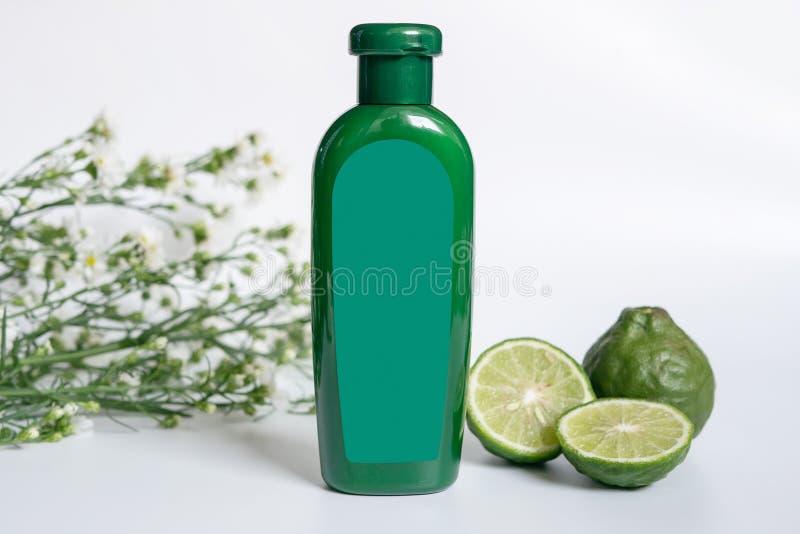 头发概念的天然产品 有空白的标签的绿色塑料瓶包含草本香柠檬香波 免版税库存照片