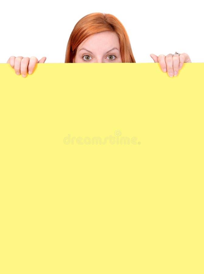 头发的超出偷看的红色墙壁妇女 免版税库存照片