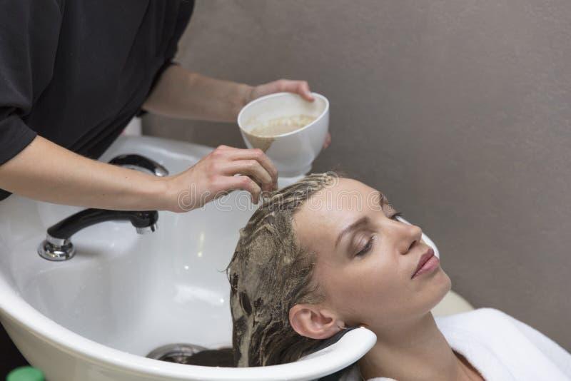 头发秀丽关心、润肤霜应用、美发师,一个美丽的女孩、自然,健康和秀丽的头发面具 库存照片
