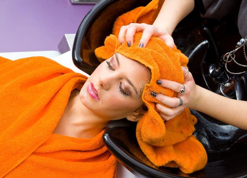 头发顶头美发师洗涤的妇女 免版税图库摄影