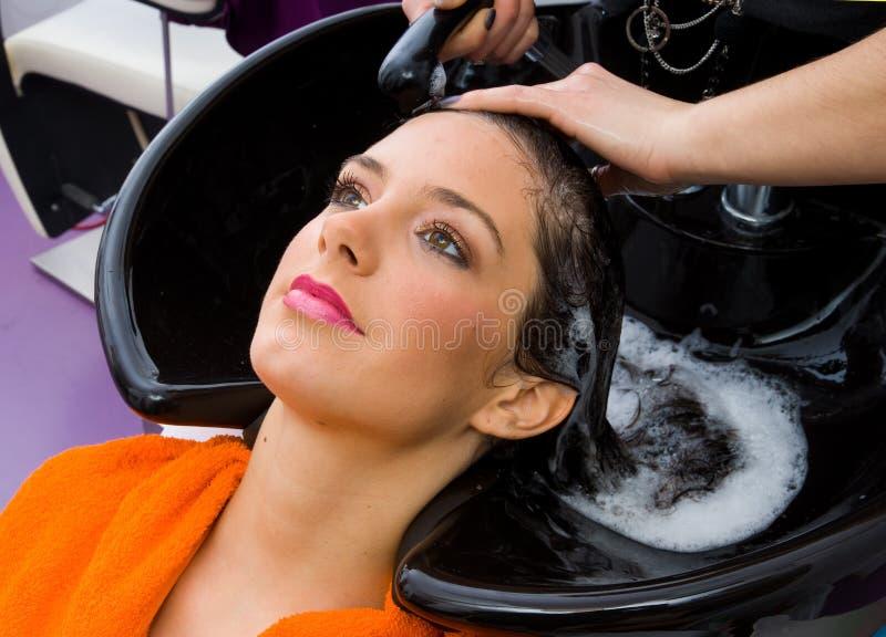 头发顶头美发师洗涤的妇女 库存图片