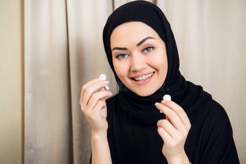 头巾或hijab的听放出的一名年轻和可爱的回教妇女的画象在她的智能手机的音乐 图库摄影