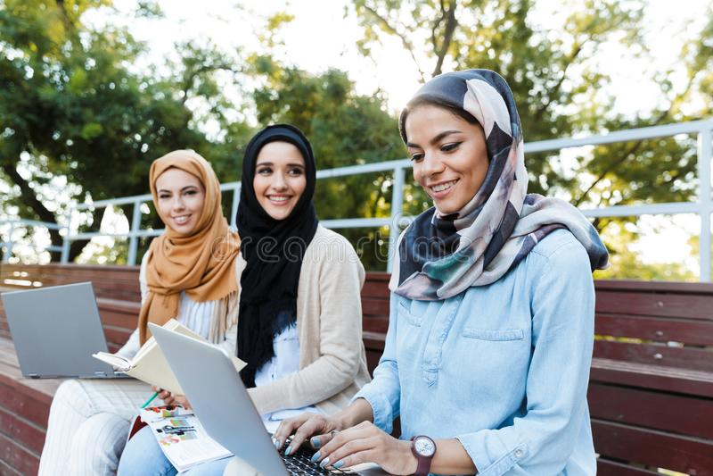 头戴头巾的三个伊斯兰教的女孩照片休息在绿色公园 免版税库存照片