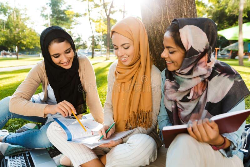 头戴头巾的三个伊斯兰教的女孩照片坐毯子在绿色公园 免版税图库摄影