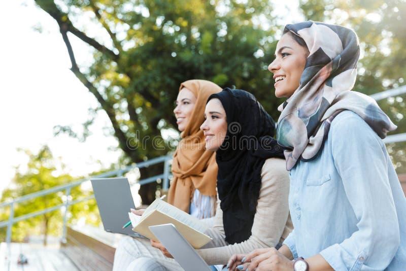 头戴头巾的三名伊斯兰教的妇女照片休息在绿色公园 免版税库存图片