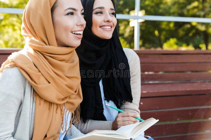头戴头巾的宗教伊斯兰教的女孩照片坐在绿色公园 免版税库存照片