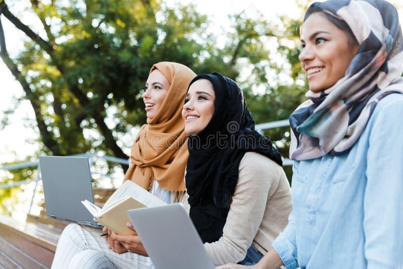 头戴头巾的年轻回教女孩照片休息在绿色公园 免版税库存照片