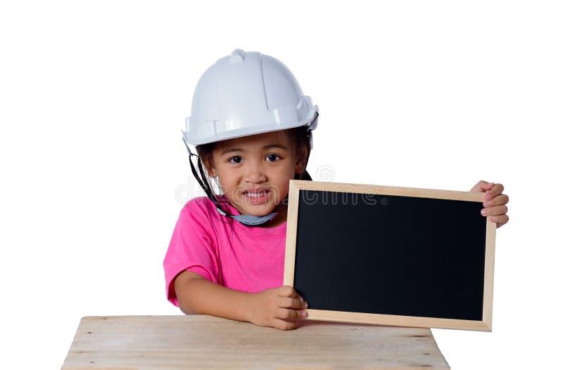 头戴安全帽和微笑与黑板的亚裔孩子隔绝在白色背景 孩子和教育概念 库存照片