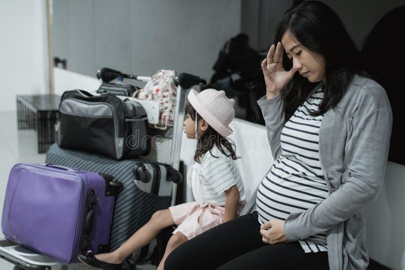头昏眼花怀孕的亚洲妇女的感受和他的女儿什么时候在休息室机场 免版税库存照片