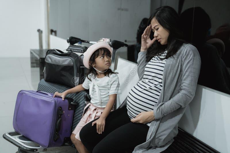 头昏眼花怀孕的亚洲妇女的感受和他的女儿什么时候在休息室机场 免版税库存图片
