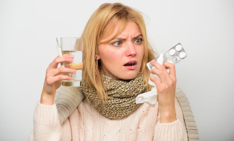 头疼和流感补救 摆脱流感 女服温暖的围巾,因为病症或流感 女孩举行玻璃水片剂 库存照片