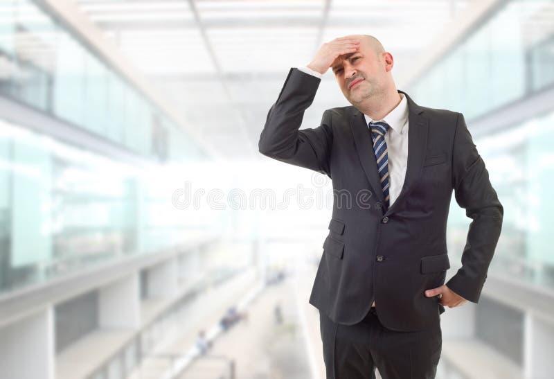 头痛。穿着西装、头痛的商人在办公室 图库摄影