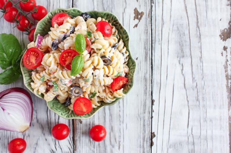 头顶可以看到西红柿、黑橄榄和菲塔,意大利面沙拉和新鲜切碎的罗勒 免版税库存照片