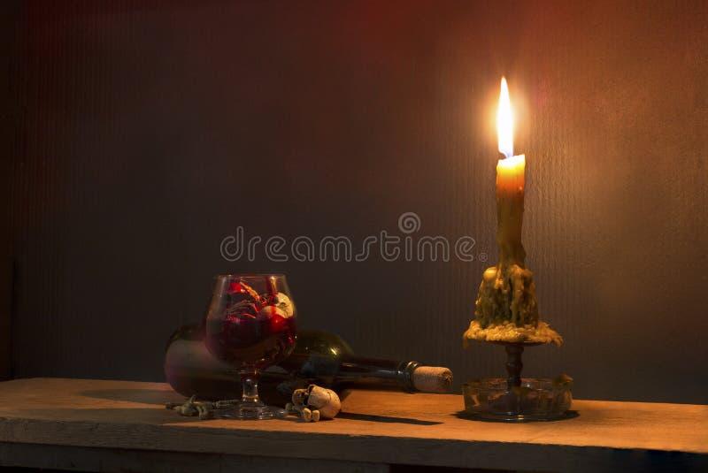 头骨在血液玻璃和蜡烛在木桌上在烛光 图库摄影