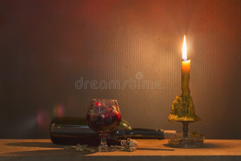 头骨在血液玻璃和蜡烛在木桌上在烛光 免版税库存图片