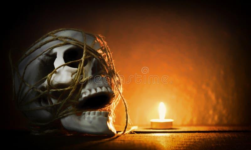 头骨静物画-有绳索的人的头骨装饰在万圣节聚会和轻的蜡烛在黑暗的背景 免版税库存照片