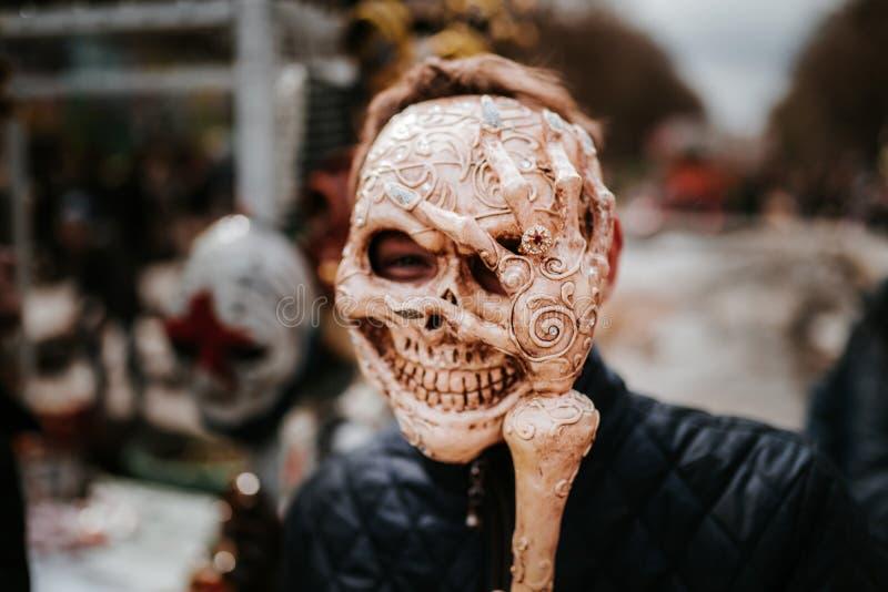 头骨面具的人在街道在狂欢节或万圣节乐团的时候 最基本的面具 免版税库存照片