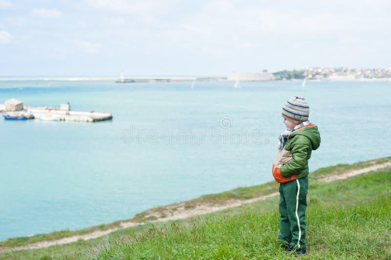 夹克和帽子的孤独的小男孩在倾斜在春天站立反对海背景  免版税库存照片