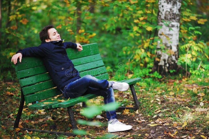 夹克和牛仔裤的可爱的深色头发的人坐长凳n 免版税库存图片