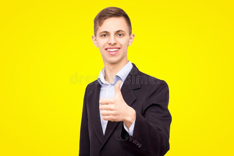 夹克和蓝色衬衣的人显示在黄色背景隔绝的一个手指 免版税库存照片