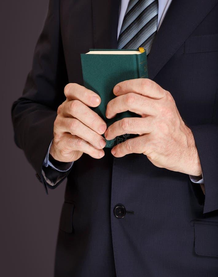 夹克的一个人在两只手中拿着在绿色盖子的一本小书 库存照片