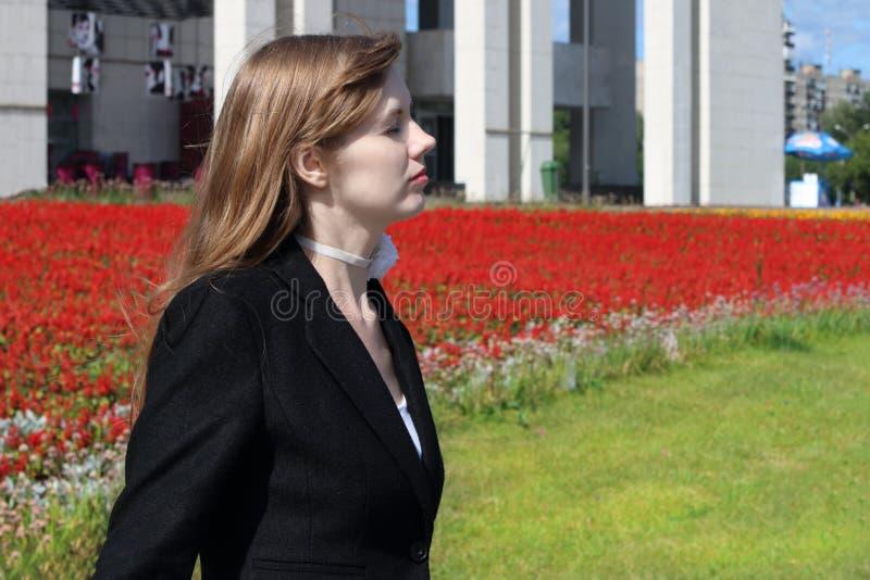 黑夹克的俏丽的妇女在红色花床附近摆在  图库摄影
