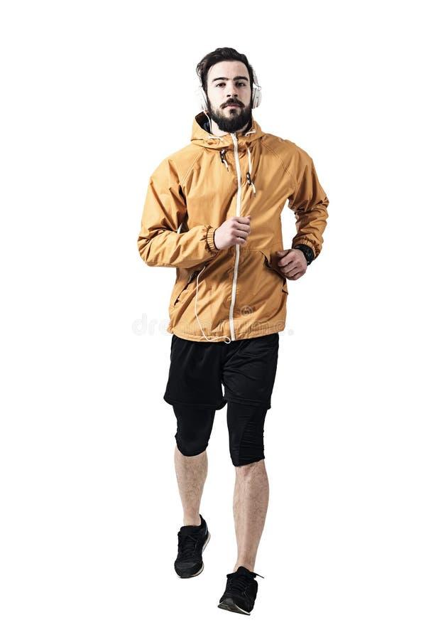 夹克的坚定的年轻慢跑者有运行往照相机的耳机的 库存图片