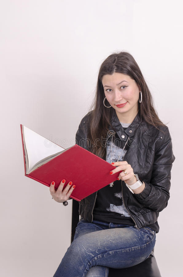 黑夹克的好亚裔女孩有一本红色书的。 库存图片
