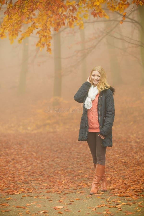 夹克的微笑的时尚白肤金发的妇女在公园 免版税库存图片
