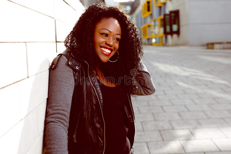 夹克的愉快的可爱的黑人妇女 免版税图库摄影