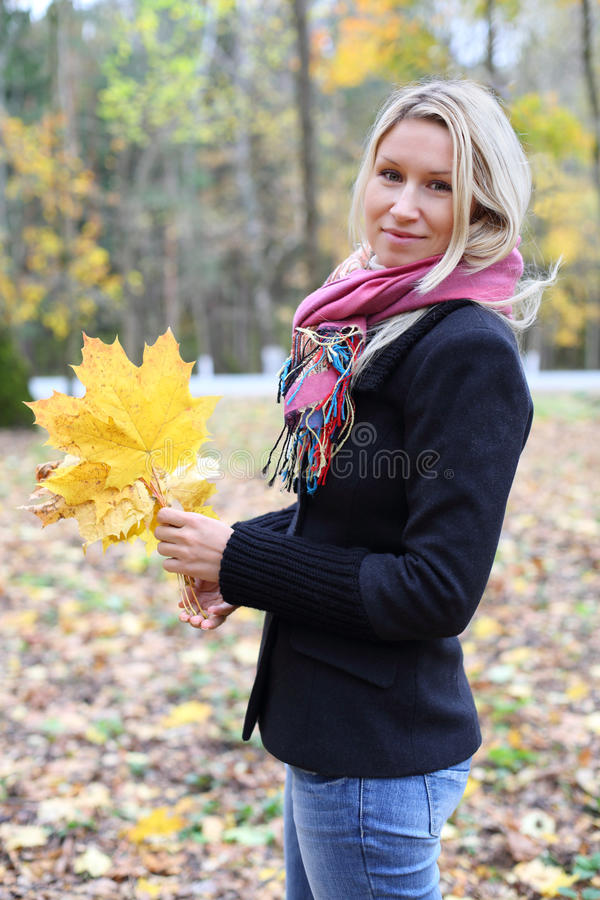 黑夹克的愉快的白肤金发的妇女在秋天森林里。 库存照片