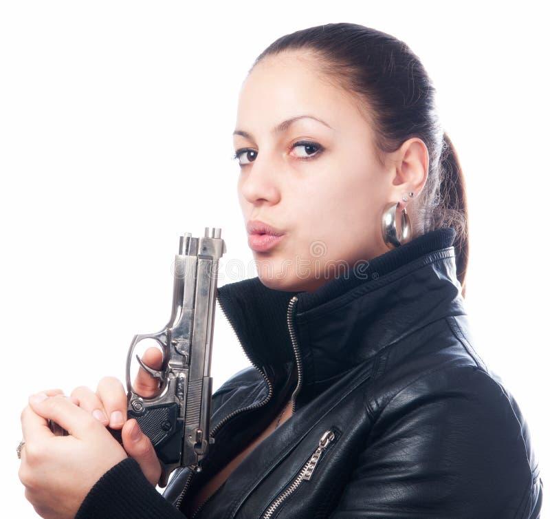 黑夹克的美丽的女孩和beretta在她的手上开枪 免版税图库摄影