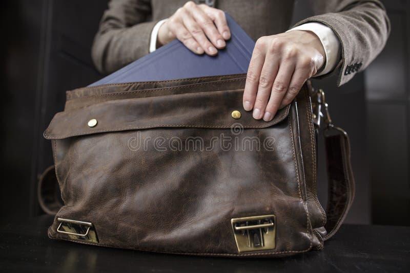夹克的老师从一个老皮革公文包得到书 库存照片