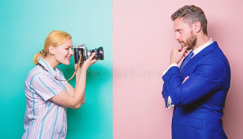 夺取信心 摆在女性摄影师前面的商人 摄影师射击的男性模型在演播室 库存照片