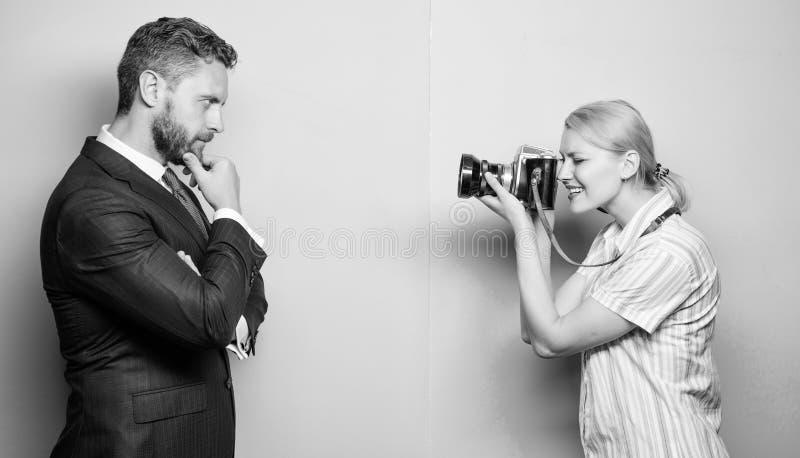 夺取信心 摆在女性摄影师前面的商人 摄影师射击的男性模型在演播室 免版税库存图片