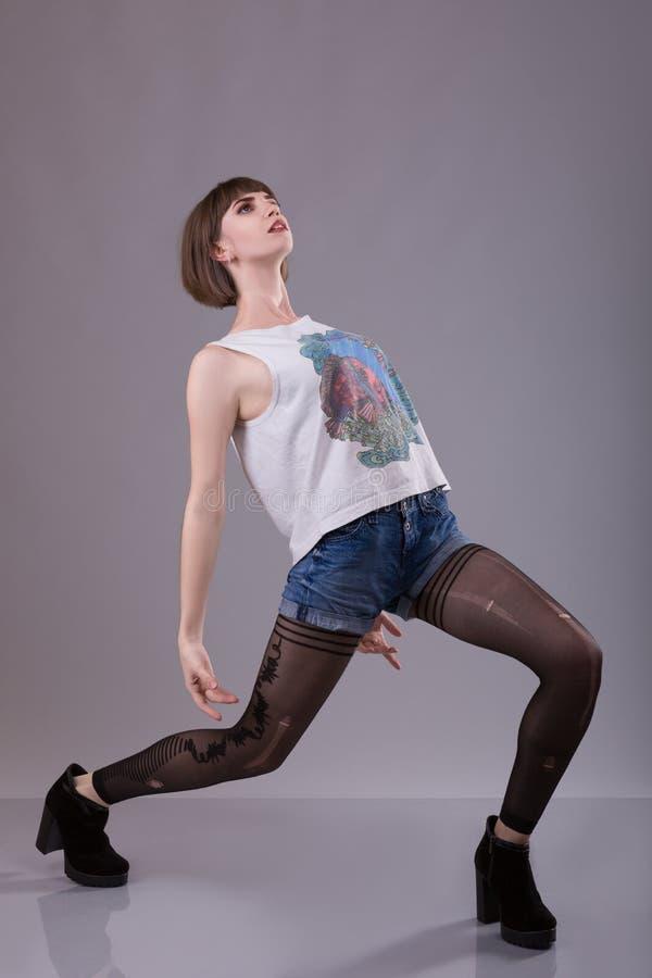 奇怪的妇女在被撕毁的裤袜下垂  库存图片