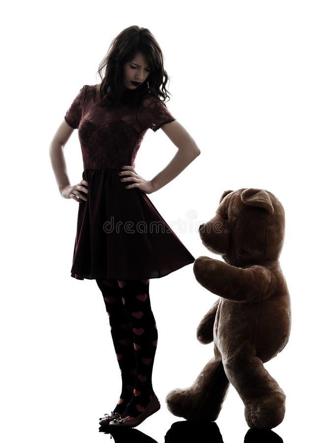 奇怪的少妇和狠毒玩具熊剪影 免版税库存照片