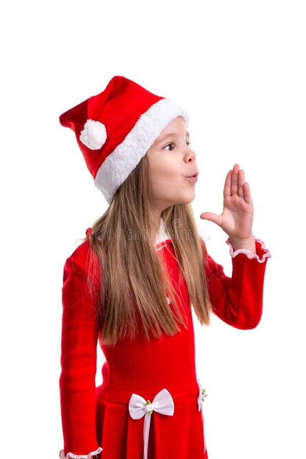 奇迹吹空气用被举的手的圣诞节女孩,戴圣诞老人帽子被隔绝在白色背景 免版税库存图片