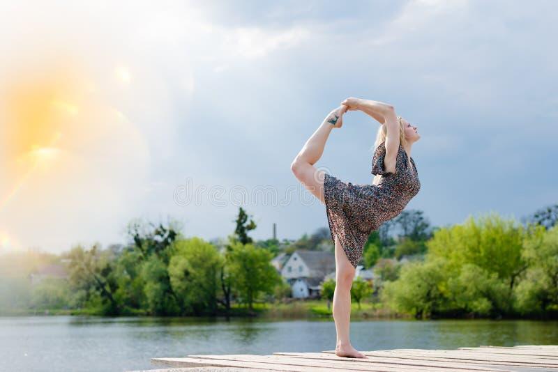 奇迹舞蹈家:美妙跳舞轻的礼服的白肤金发的女孩的图象在光线阳光蓝天的水湖户外 免版税库存图片