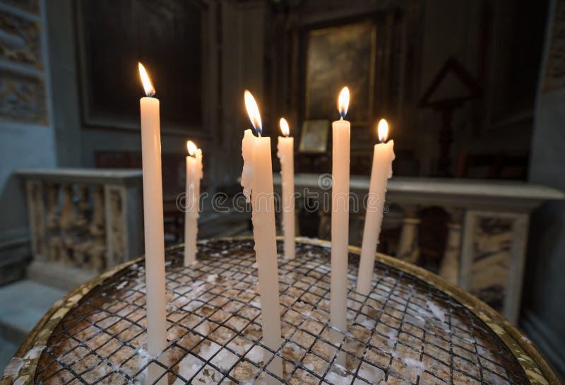 奉献或祷告蜡烛在天主教堂里 库存图片