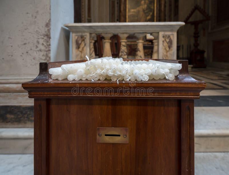 奉献或祷告蜡烛在天主教堂里 库存照片