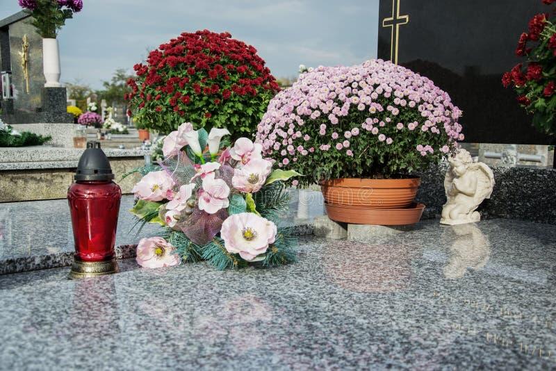奉献的蜡烛在坟茔石头的灯笼和菊花花在坟园 坟墓,在传统公墓的墓碑 免版税库存图片